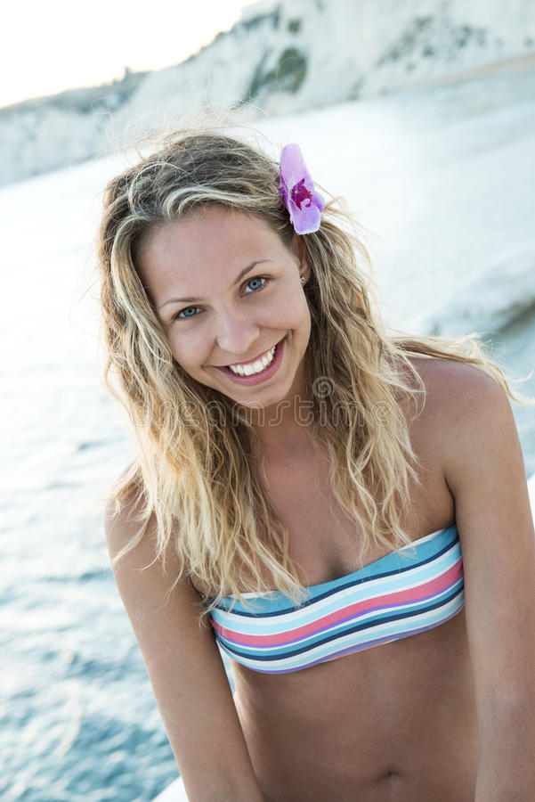 La fille blonde s'assied sur une roche blanche par la mer photos stock