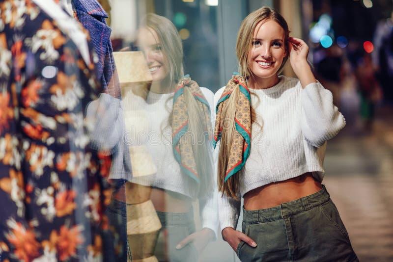 La fille blonde souriant avec la ville urbaine defocused s'allume la nuit photographie stock