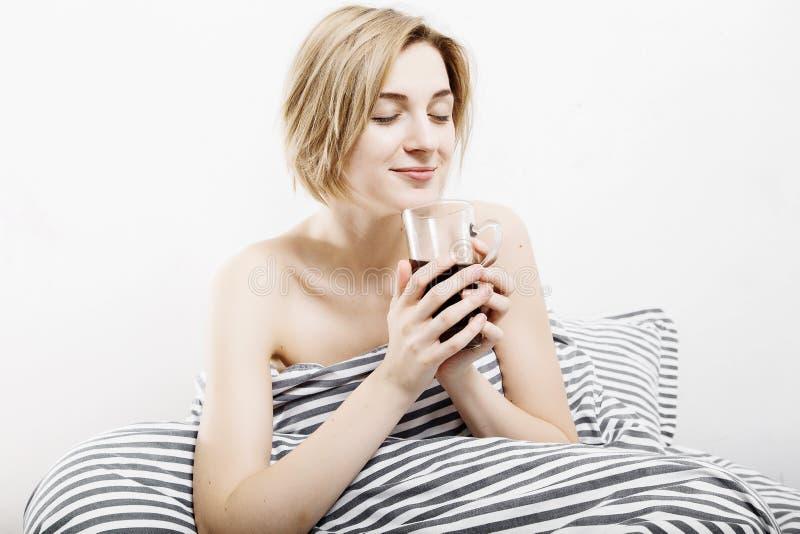 La fille boit du café dans le lit Fille de matin où la jeune fille réveille pendant le matin sommeil Matin se réveillant Lisant l photo libre de droits
