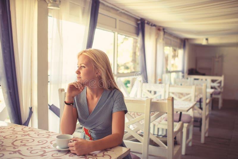 La fille boit du café ou du thé dans le café ou le restaurant photographie stock