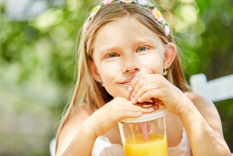 La fille boit du jus d'orange avec la paille image stock
