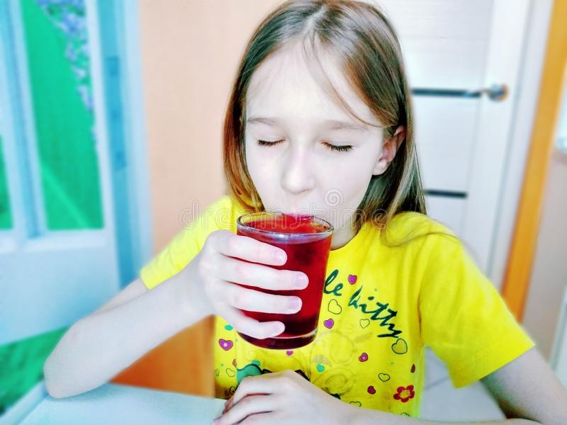 La fille boit l'eau avec des morceaux de glace de fruit photographie stock libre de droits