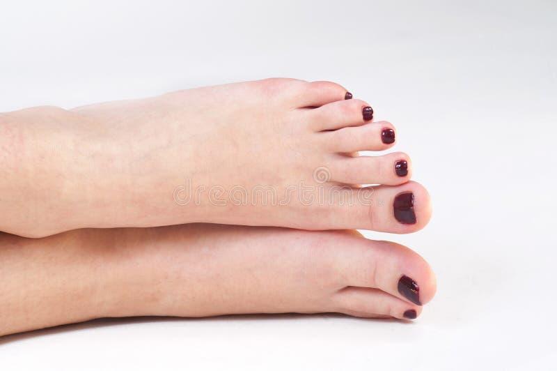 La fille botte assez le vernis à ongles avec la pointe du pied photos stock