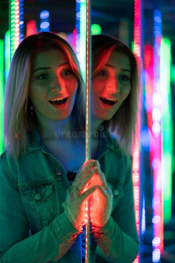 La fille caucasienne douce marche dans un labyrinthe de miroir avec les diodes colorées et apprécie une salle peu commune d'attra image stock
