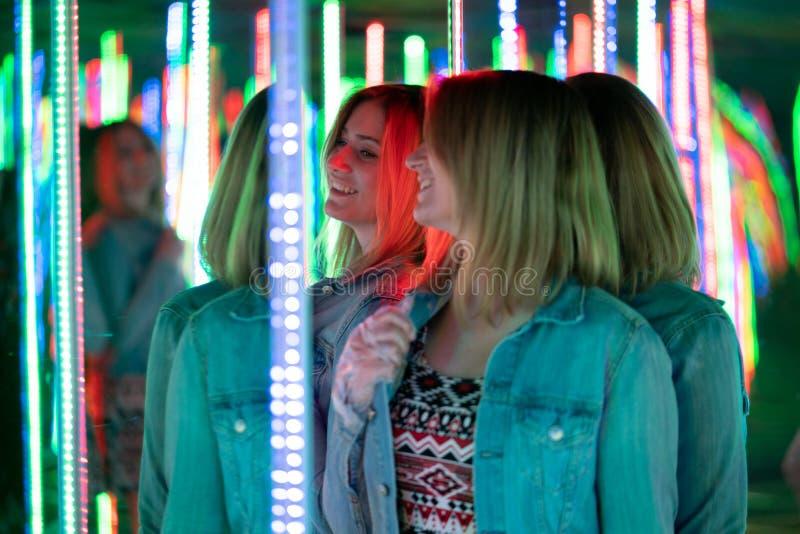 La fille caucasienne douce marche dans un labyrinthe de miroir avec les diodes color?es et appr?cie une salle peu commune d'attra photo stock