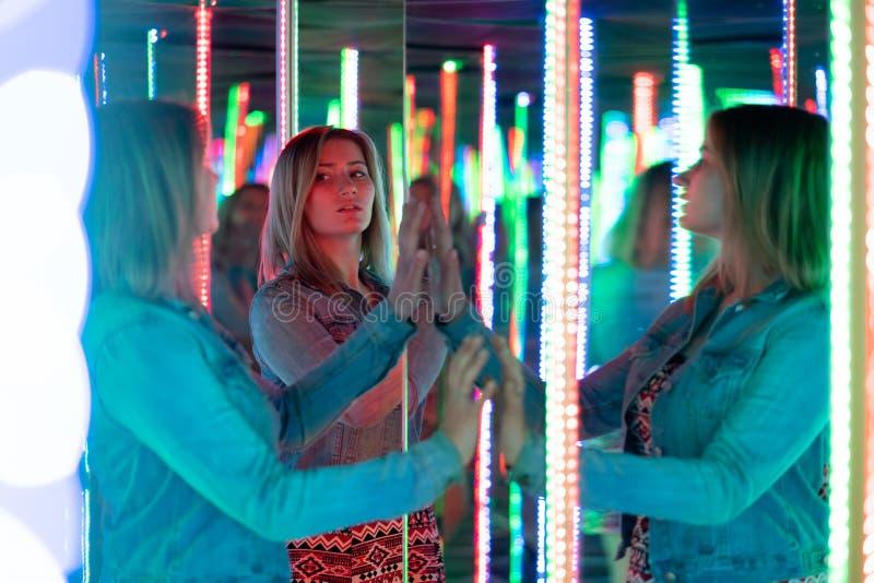 La fille caucasienne douce marche dans un labyrinthe de miroir avec les diodes color?es et appr?cie une salle peu commune d'attra photos stock