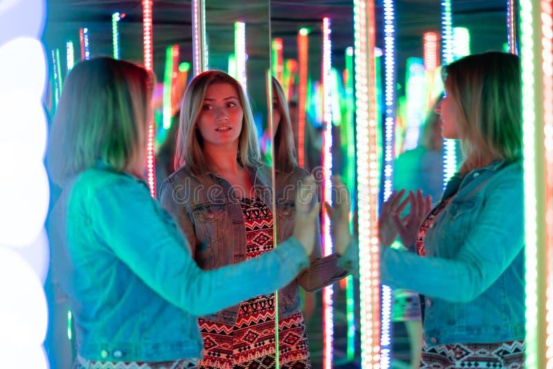 La fille caucasienne douce marche dans un labyrinthe de miroir avec les diodes color?es et appr?cie une salle peu commune d'attra photographie stock