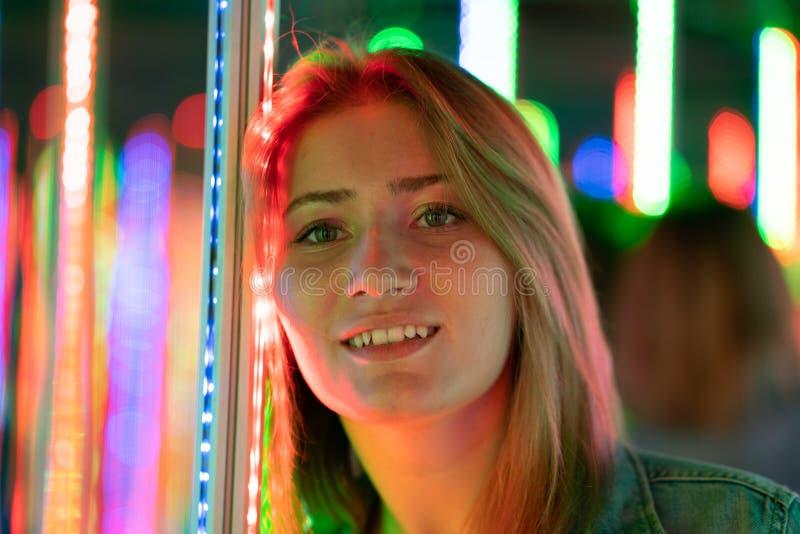 La fille caucasienne douce marche dans un labyrinthe de miroir avec les diodes color?es et appr?cie une salle peu commune d'attra image libre de droits