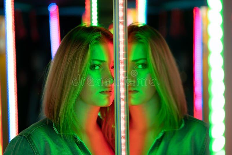 La fille caucasienne douce marche dans un labyrinthe de miroir avec les diodes color?es et appr?cie une salle peu commune d'attra image stock