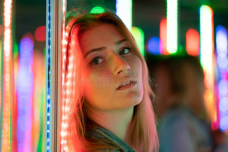 La fille caucasienne douce marche dans un labyrinthe de miroir avec les diodes color?es et appr?cie une salle peu commune d'attra images stock