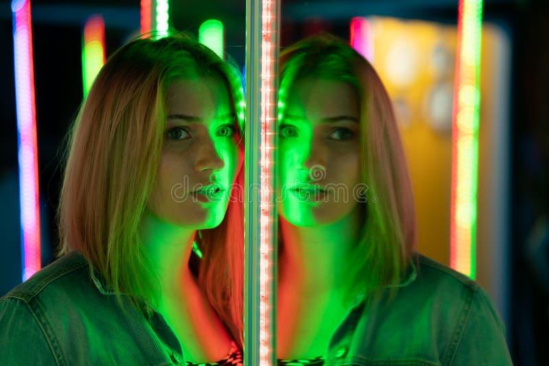 La fille caucasienne douce marche dans un labyrinthe de miroir avec les diodes color?es et appr?cie une salle peu commune d'attra photo libre de droits