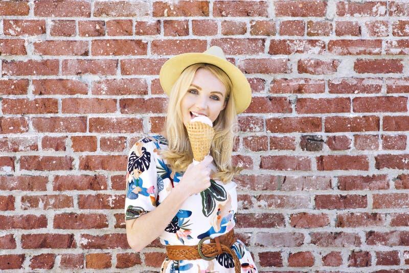 La fille caucasienne millénaire lèche une crème glacée un jour chaud d'été tout en souriant photo libre de droits