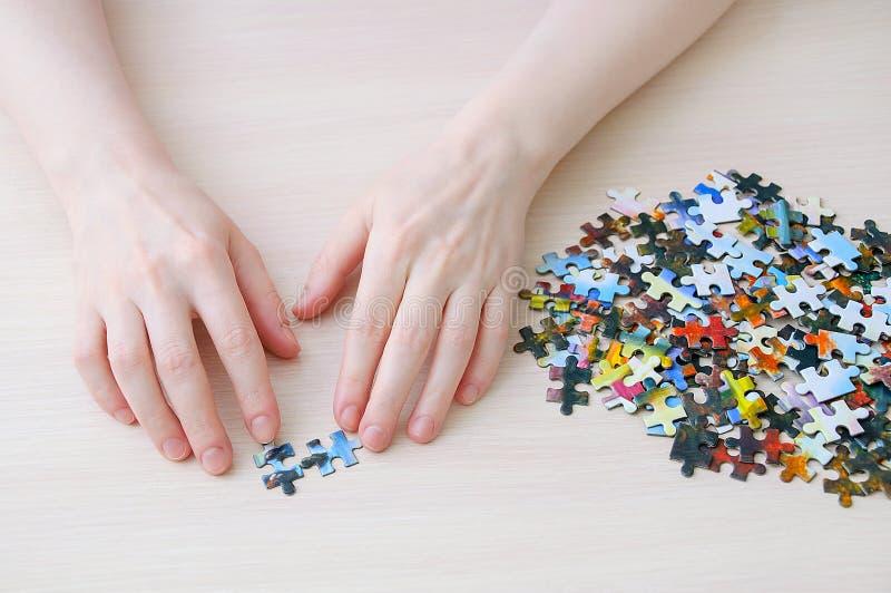 La fille caucasienne rassemble des puzzles sur la table Vue de ci-avant images stock