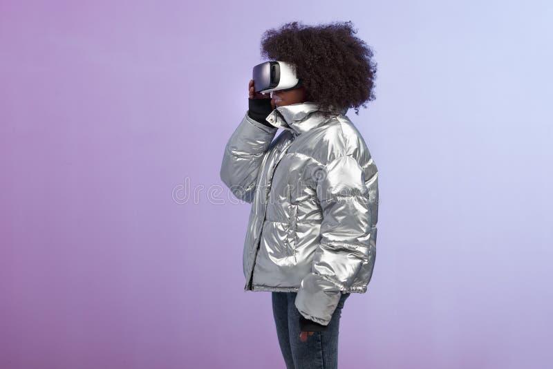 La fille châtain bouclée à la mode habillée dans une veste de couleur argent emploie les verres de réalité virtuelle dans le stud image stock