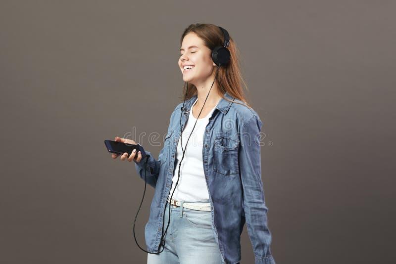 La fille châtain de sourire habillée dans un T-shirt blanc, les jeans et la chemise de jeans tient le téléphone dans sa main et é photos libres de droits