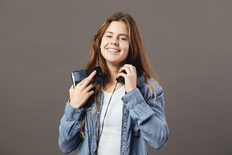 La fille châtain de sourire habillée dans un T-shirt et une chemise blancs de jeans tient le téléphone dans sa main et écoute que photographie stock
