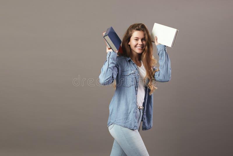 La fille châtain drôle habillée dans un T-shirt blanc, des jeans et des jeans tient des livres dans des ses mains sur un fond gri photos libres de droits