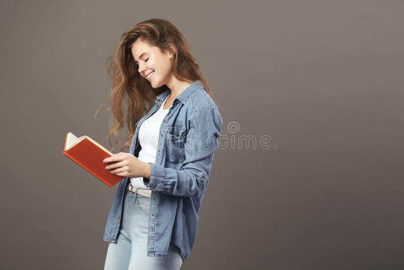 La fille châtain habillée dans un T-shirt blanc, des jeans et des jeans lit un livre sur un fond gris photo stock