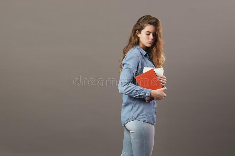 La fille châtain habillée dans un T-shirt blanc, des jeans et des jeans tient des livres dans des ses mains sur un fond gris photos libres de droits
