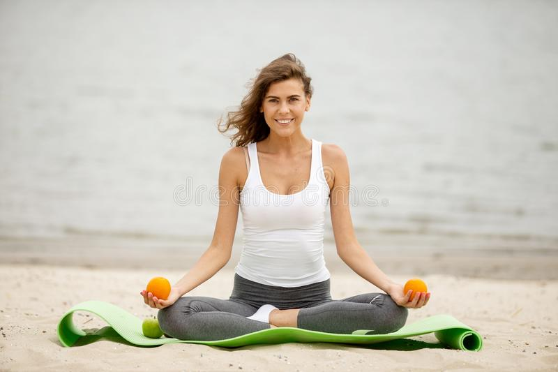 La fille châtain mince tient des oranges dans des ses mains situant en position de lotus sur un tapis de yoga sur la plage sablon image stock