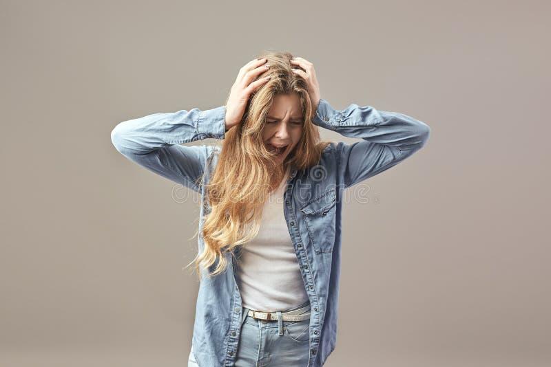 La fille châtain triste habillée dans un T-shirt et un treillis blancs tient ses mains sur sa tête et cris sur un fond gris photos libres de droits