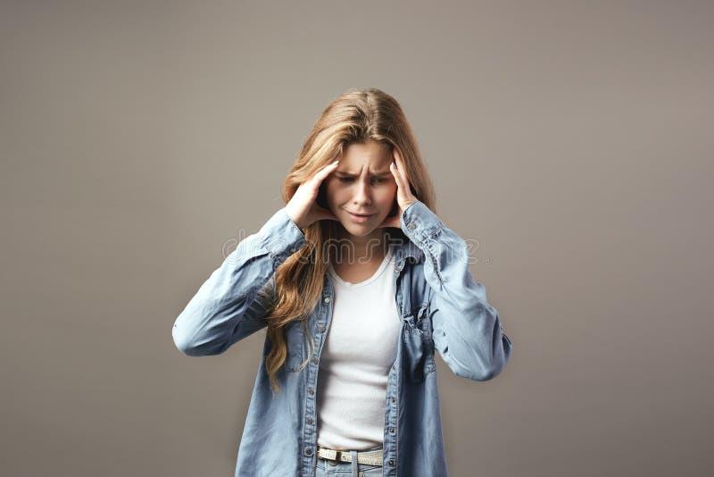La fille châtain triste habillée dans un T-shirt et un treillis blancs tient ses mains sur sa tête sur un fond gris image libre de droits