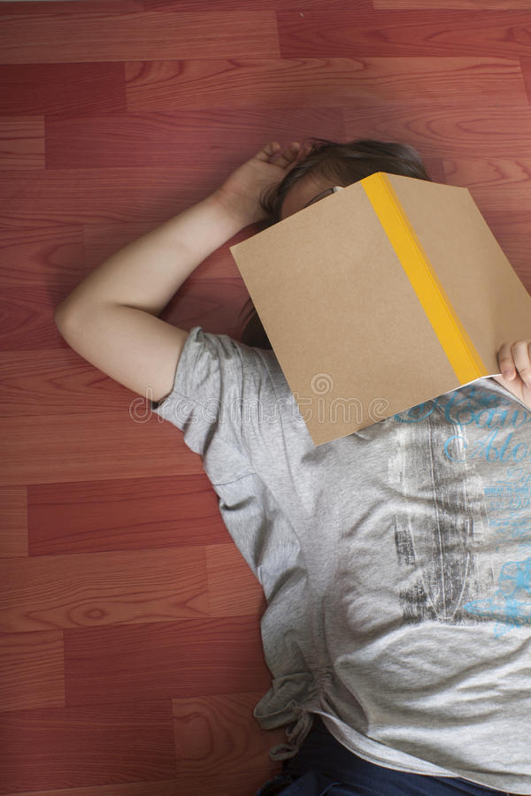 La fille chinoise est fatiguée pour regarder le notbook et pour tomber endormi sur le plancher photographie stock