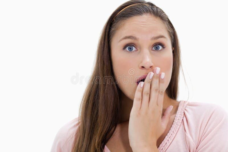 La fille choquée avec elle remettent sa bouche photo stock