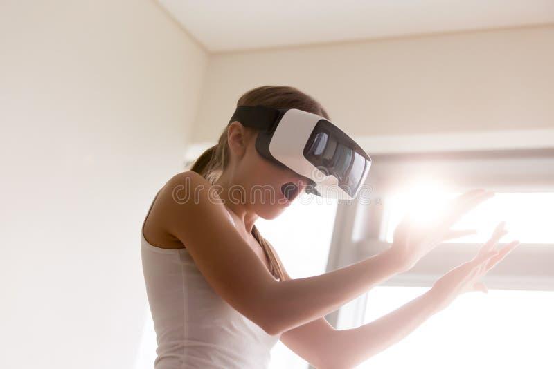 La fille choquée regardant des mains par des lunettes, le premier VR experien photographie stock libre de droits