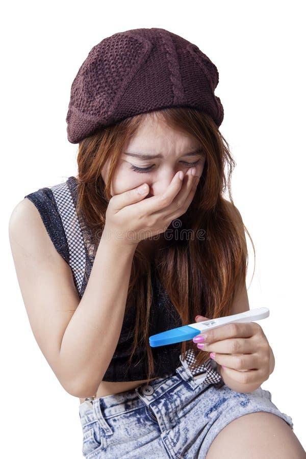 La fille choquée tient l'essai de grossesse photographie stock libre de droits
