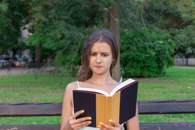 La fille confuse et contrariée lit un livre sur le banc en parc photographie stock libre de droits