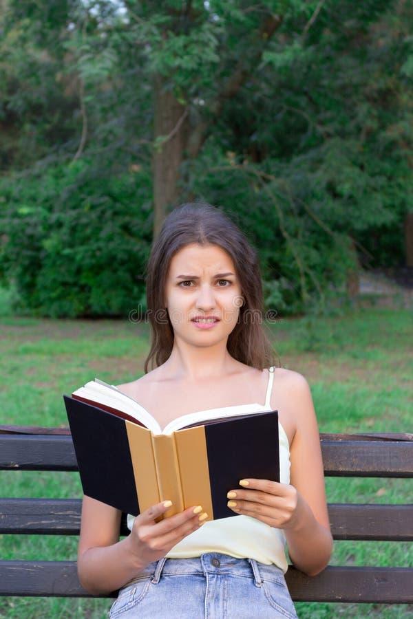 La fille confuse et contrariée lit un livre sur le banc en parc photos stock