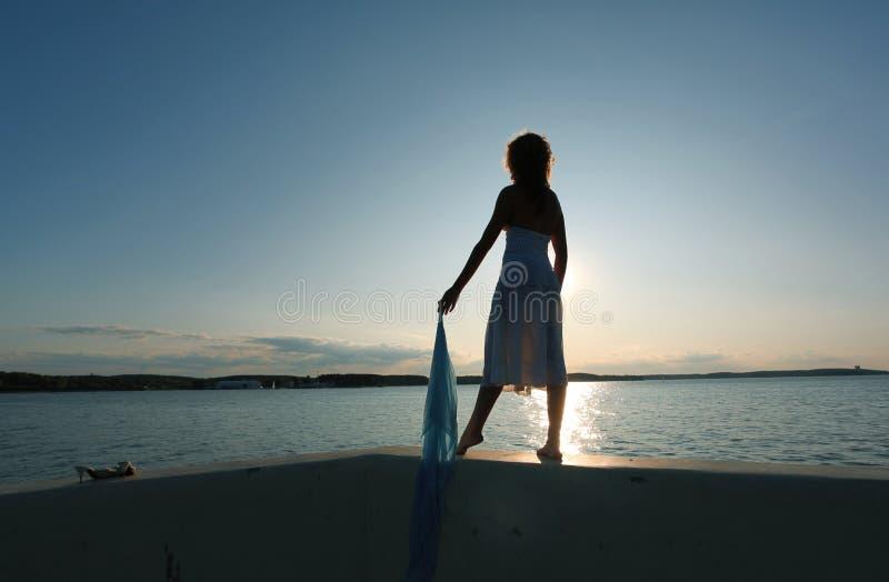 La fille contacte le coucher du soleil images stock