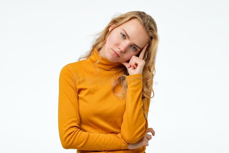 La fille contrariée ennuyée avec les cheveux blonds regardant la caméra est devenue fatiguée à l'école photographie stock