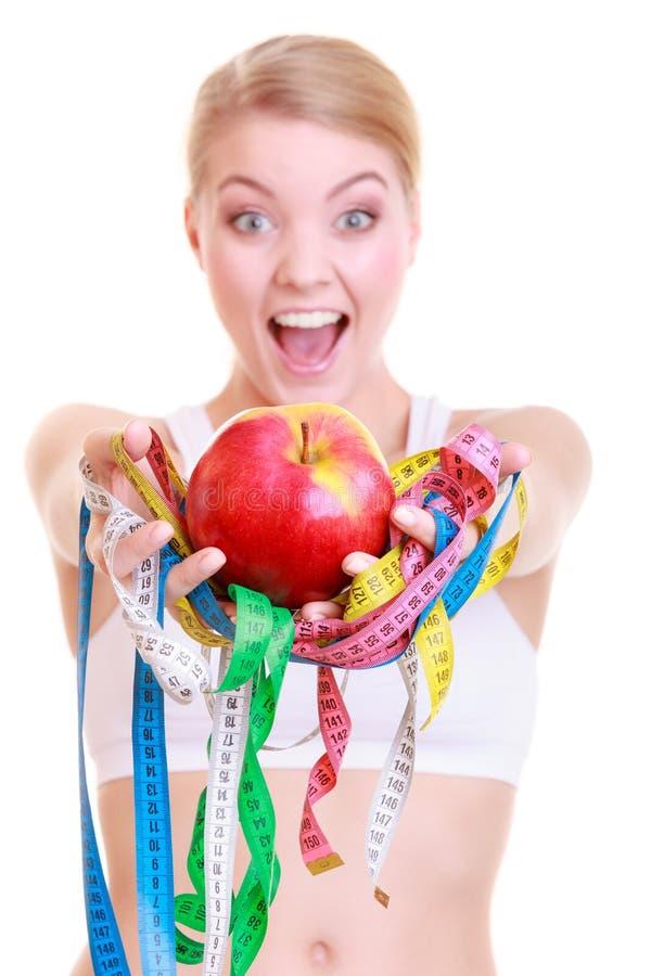 La fille convenable de femme de forme physique tenant la mesure colorée attache du ruban adhésif au fruit images stock