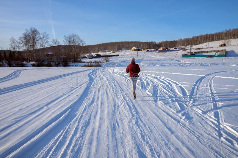La fille court le long d'une route d'hiver sur un lac congelé vers un village sur une colline, un jour ensoleillé d'hiver photographie stock libre de droits