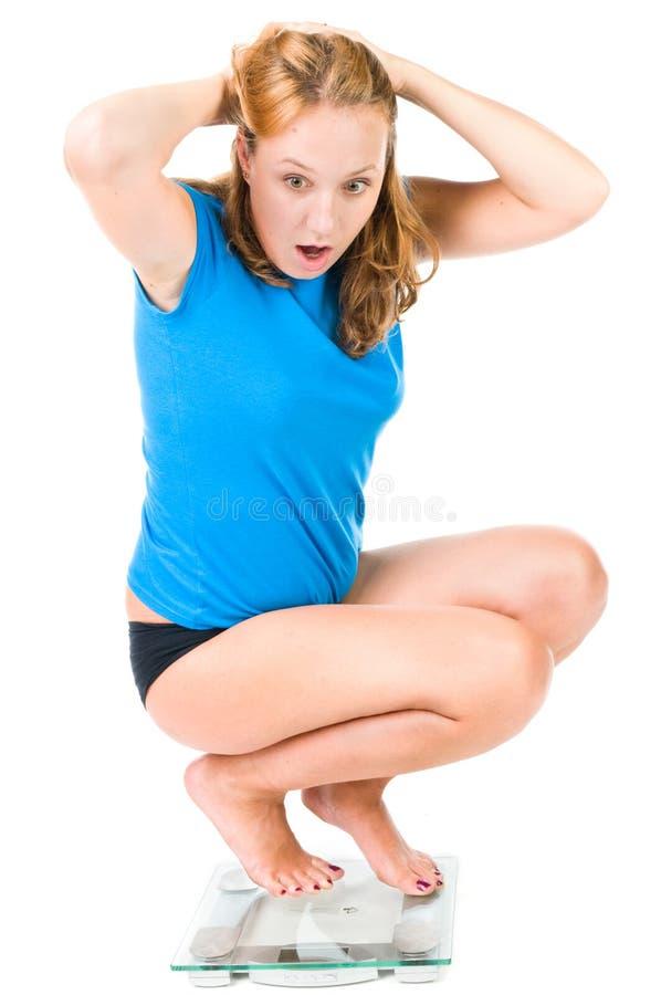 La fille crie pendant qu'elle voit son poids sur l'échelle photos stock