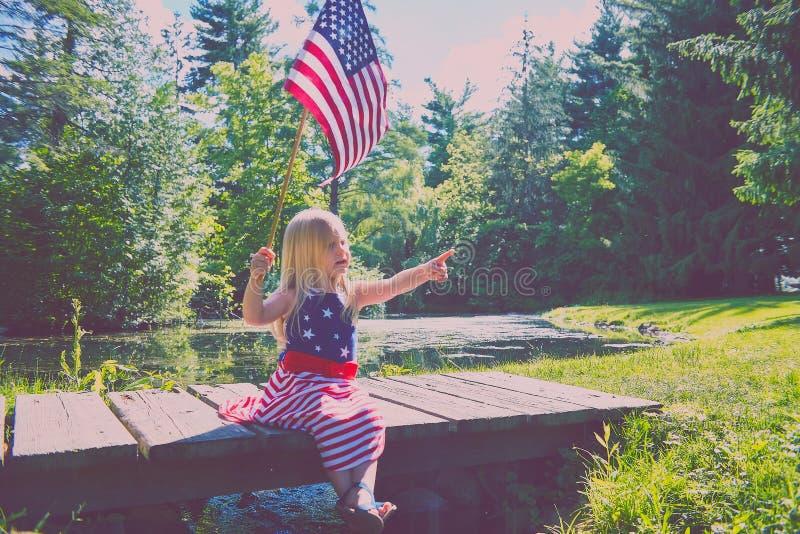 La fille curieuse avec les Etats-Unis marquent se reposer sur le pont en bois image stock