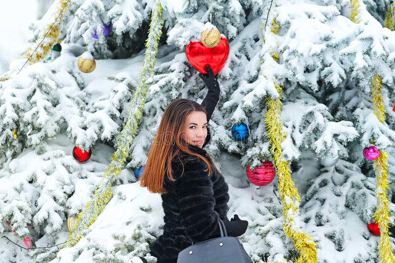 La fille décore des boules d'un arbre de Noël photo stock