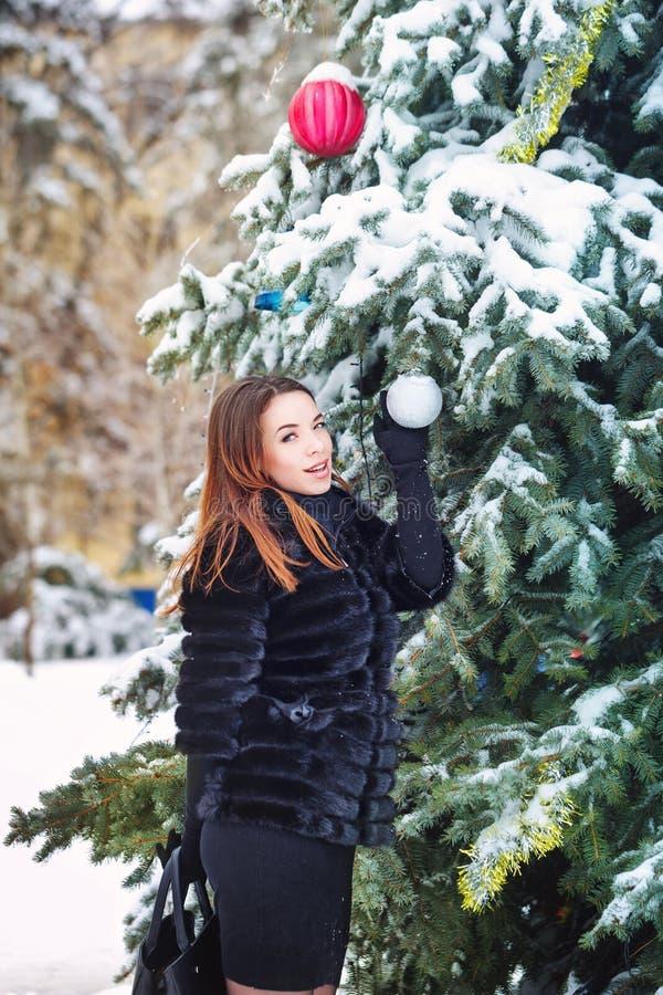 La fille décore des boules d'un arbre de Noël image stock