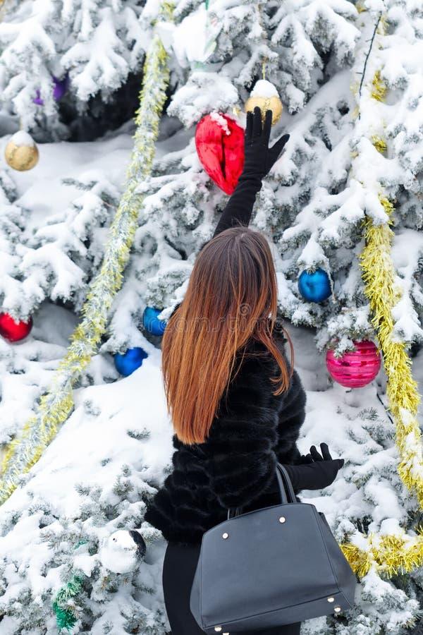 La fille décore les jouets d'arbre de Noël images stock