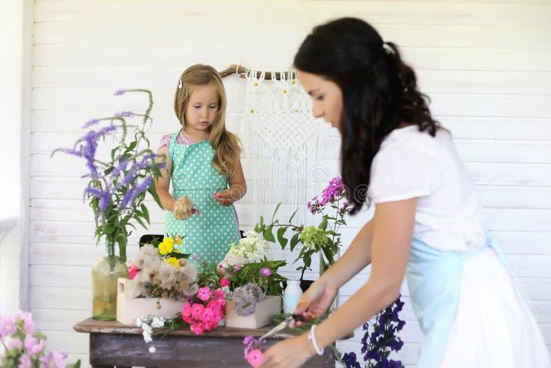 La fille décore un bouquet des fleurs sèches photographie stock