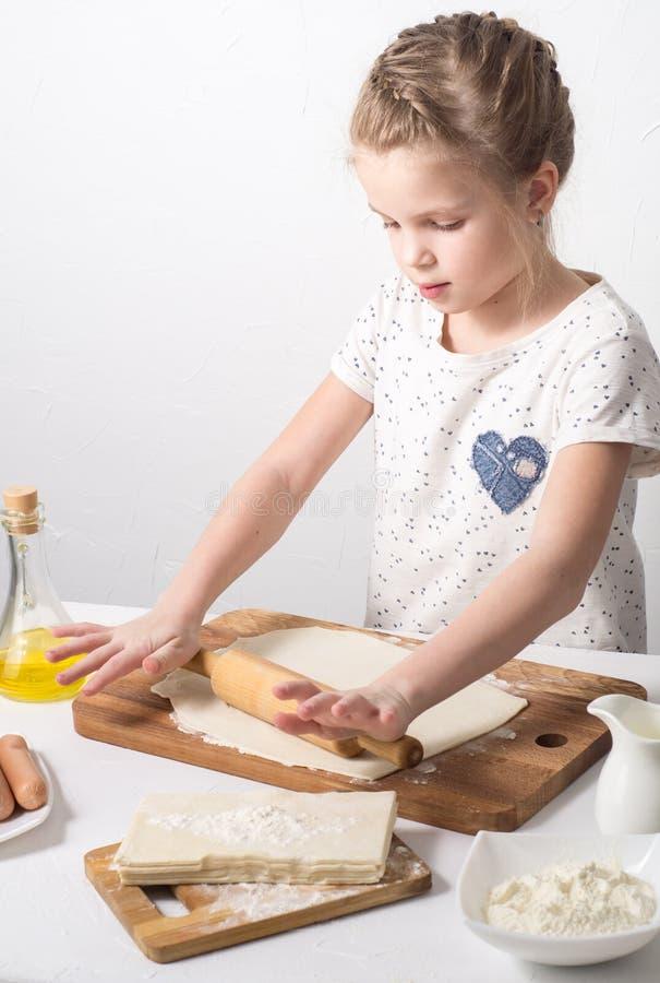 La fille déroule la pâte pour faire avec cuire au four une goupille photo stock