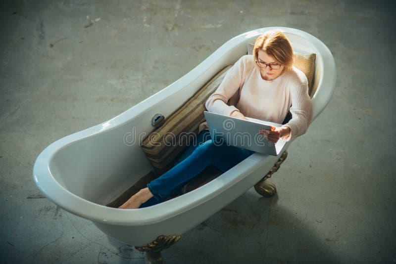 La fille détendent dans la baignoire avec l'ordinateur portable gardent le blog Affaires et communication agiles Achetez le marke image stock