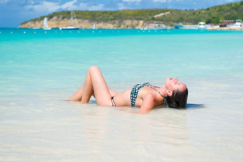 La fille détendent dans l'eau transparente de mer ou d'océan à l'Antigua images libres de droits