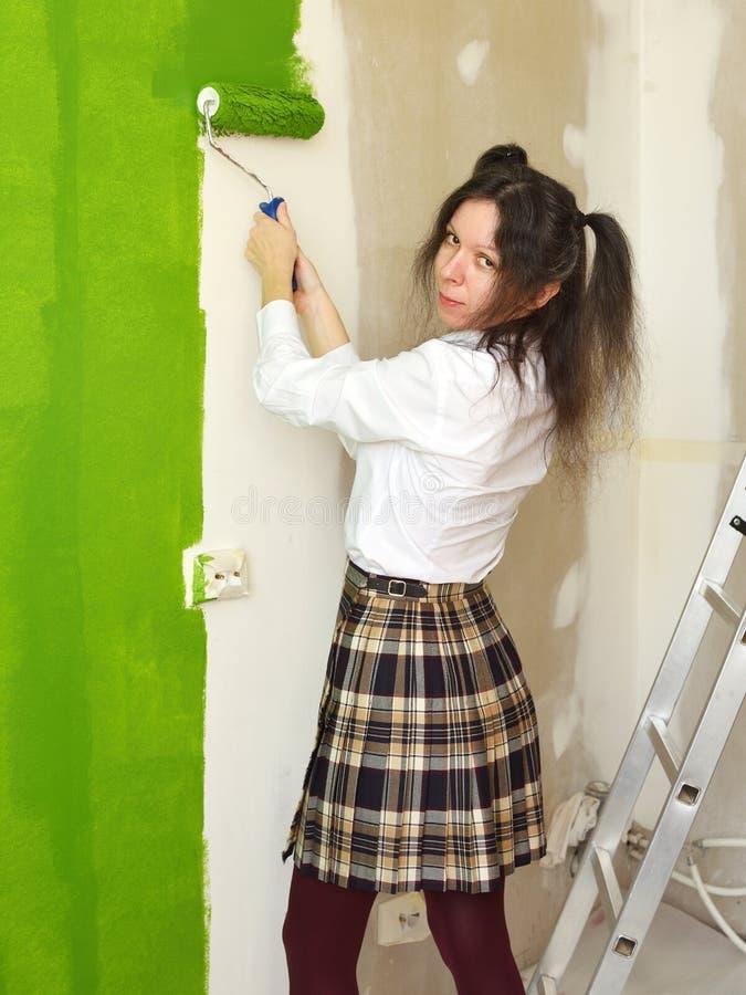 La fille d'école essaye de peindre un mur en vert avec un rouleau image stock