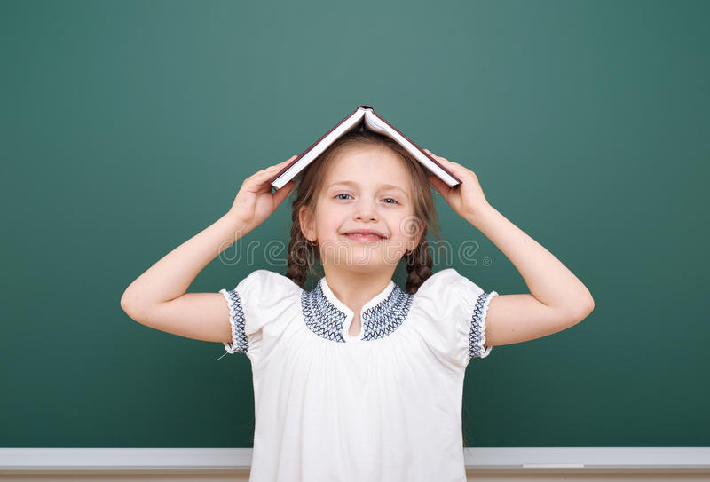 La fille d'école a lu le livre, posant au conseil pédagogique, l'espace vide, concept d'éducation photos stock