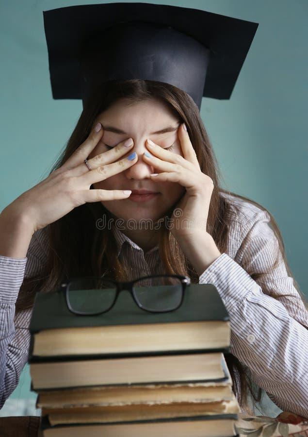 La fille d'étudiant d'adolescent dans le chapeau d'obtention du diplôme avec la pile de bood a fatigué des yeux photographie stock libre de droits