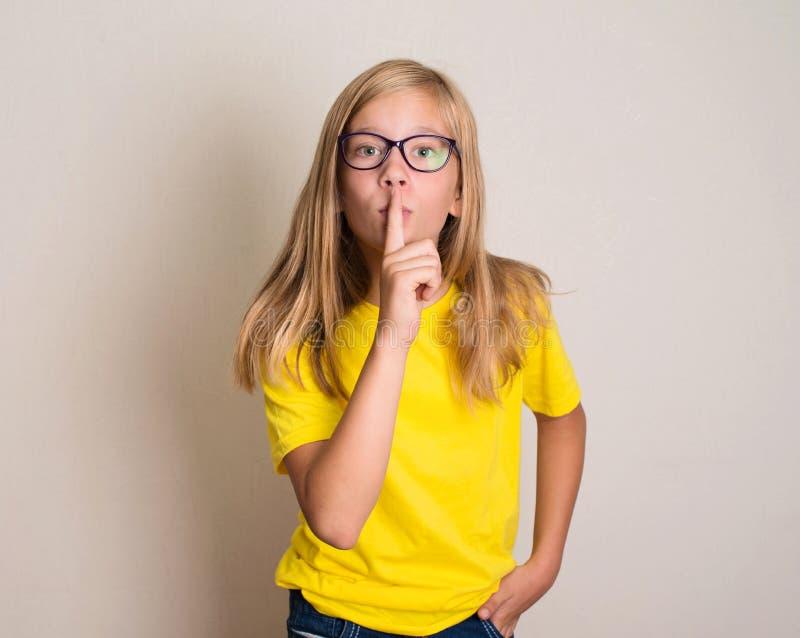 La fille d'adolescent dans des lunettes mettant le doigt jusqu'aux lèvres et demandent le SI photos stock