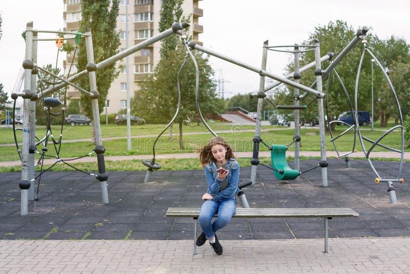 La fille d'adolescent surfe l'Internet avec le sitti de téléphone portable d'iphone photos libres de droits